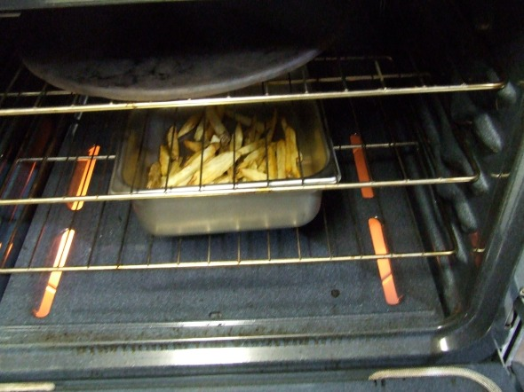 A stainless steel pan in the 275 degree oven, keeps the potatoes warm and crunchy